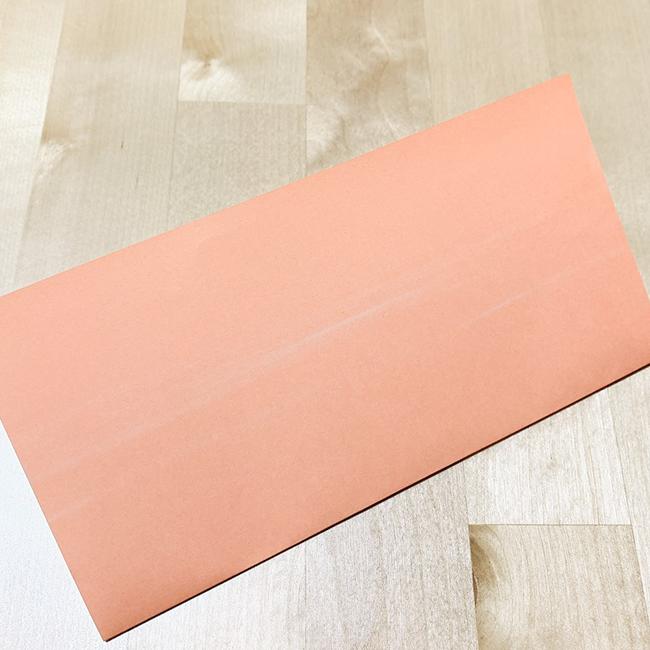 肌色折り紙を横に折り、折り目を付けます。