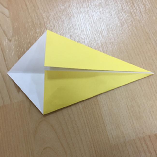 裏にして対角線に折り目をつけ真ん中に折り合わせます。