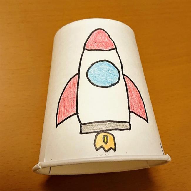 切り込みを入れた紙コップにロケットの絵を描きます。