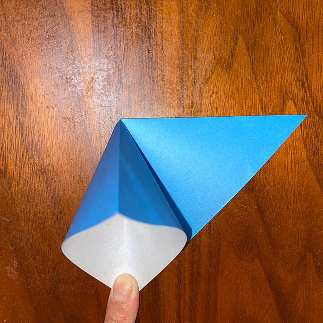 上の紙1枚を持って開き、上の角と下の角を合わせて潰して折る。