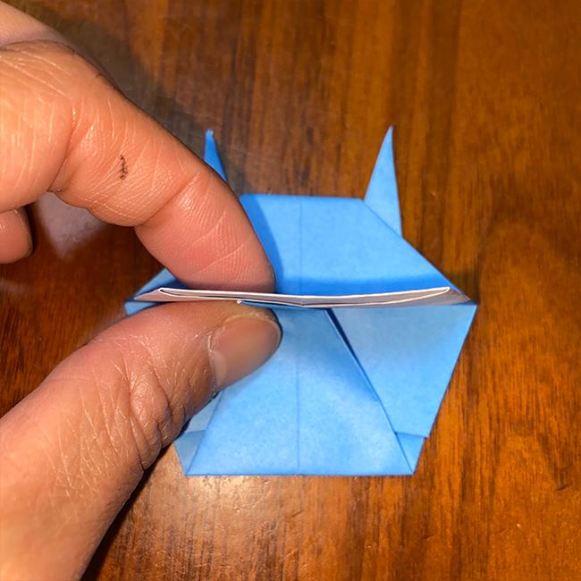 下の角を赤い線で折り、1枚めくって、中に折り込む
