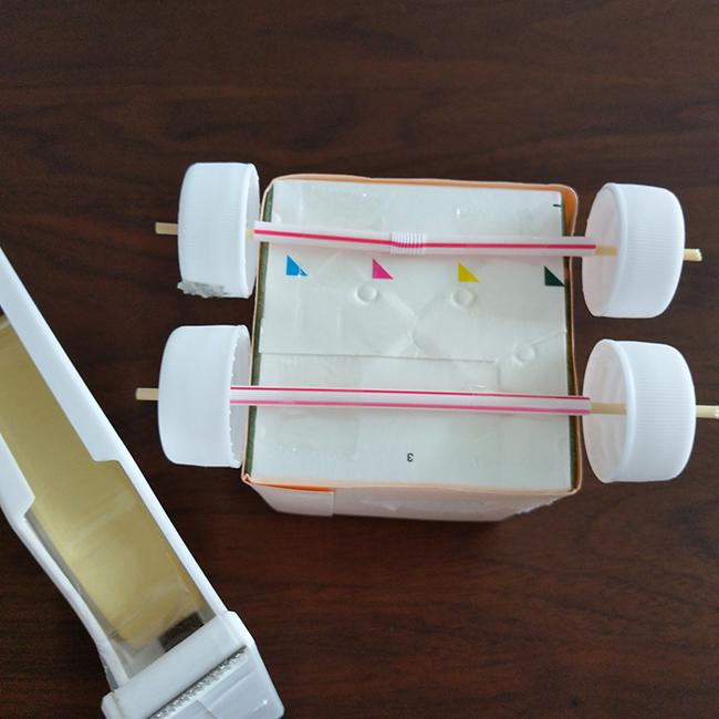 牛乳パックの底にタイヤをテープ」で固定します。